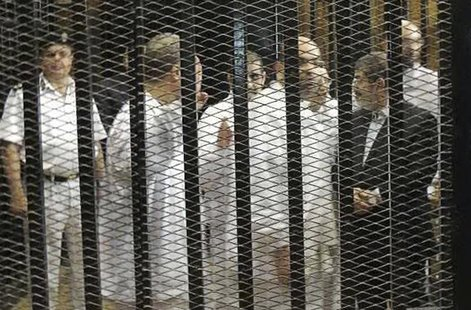 Ousted former Egyptian president Mohamed Mursi (R) speaks with other senior figures of the Muslim Brotherhood in a cage in a courthouse on t