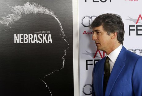 "Director Alexander Payne poses next to the poster for his film as he arrives for a gala screening of his new film ""Nebraska"" at the AFI Fest"