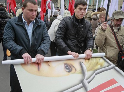 Opposition supporters roll a banner with the portrait of jailed former prime minister Yulia Tymoshenko after a rally in front of the Parliam