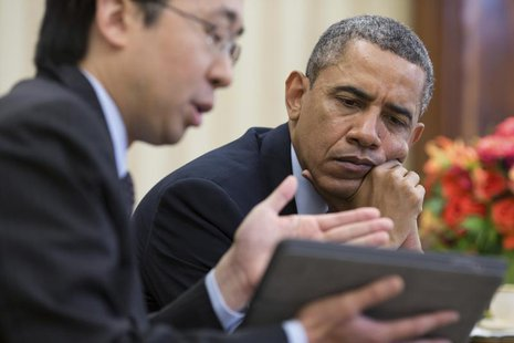 U.S. President Barack Obama watches as Todd Park (L), Assistant to the President and Chief Technology Officer, shows him information on a ta