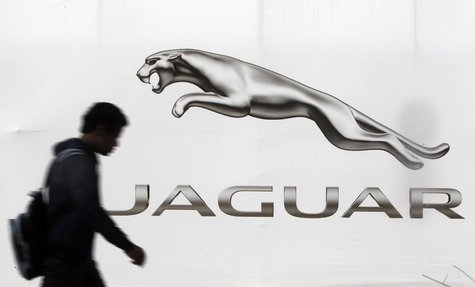 A man walks past a billboard advertising Jaguar in New Delhi February 12, 2013. REUTERS/Mansi Thapliyal