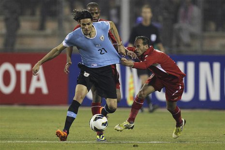 Edinson Cavani of Uruguay (L) fights for the ball with Adnan Adous of Jordan during their World Cup qualifying playoff first leg soccer matc