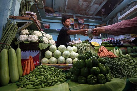A vendor accepts money from a customer at his vegetable stall at a wholesale fruit and vegetable market in Mumbai April 14, 2013. REUTERS/Vi