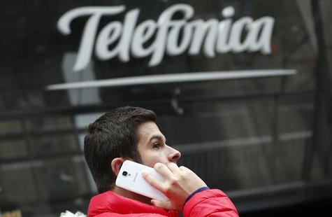 A man talks on a mobile phone as he walks past Spanish telecom group Telefonica's flagship store in central Madrid November 8, 2013. REUTERS