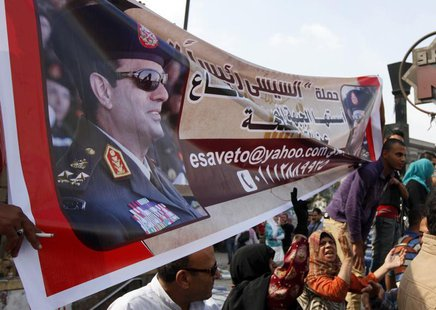 Supporters of the military hold a banner of Army chief General Abdel Fattah al-Sisi outside the Egyptian High Court in Cairo November 4, 201