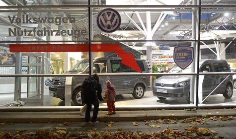 A woman and a child look at cars of German carmaker Volkswagen in a shop of a VW dealership in Hamburg, October 28, 2013. Volkswagen is due