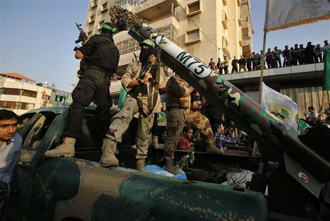 Palestinian Hamas militants stand next to M-75 home made rocket as they take part in a military parade marking the first anniversary of the