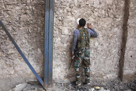 A Fighter from Tawhid Brigade, which operates under the Free Syrian Army, looks through a hole in the wall in Base 80 area of Aleppo, Novemb