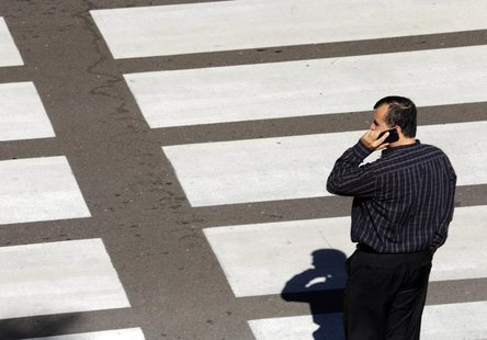 A man talks on his mobile phone as he waits at a crosswalk at Lindbergh Field Airport in San Diego, California, November 6, 2013. REUTERS/Mi