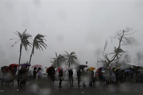 Survivors queue during a downpour to charge their mobile phones at a government-provided power generator in the aftermath of super typhoon H