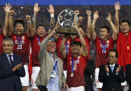 China's Guangzhou Evergrande coach Marcello Lippi (front 2nd L) and player Zheng Zhi (10) hold up the trophy after winning their final match