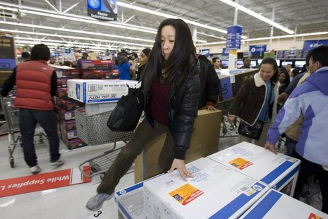 A woman jumps over computers at a Walmart store in Oakland, California, November 28, 2008. REUTERS/Kimberly White