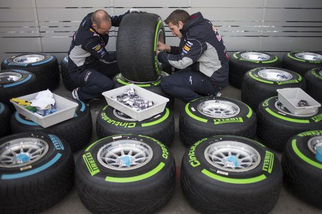 Red Bull Formula One team members check tires at the Circuit of the Americas in Austin, Texas November 14, 2013. The U.S. Grand Prix will ta