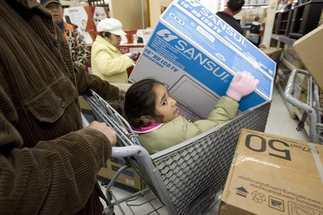 A girl sits in a shopping cart as she holds a television in a Walmart store in Oakland, California, November 28, 2008. REUTERS/Kimberly Whit