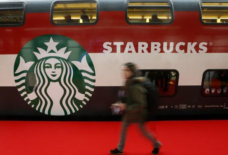 A woman walks past a Starbucks logo painted on a railway coach at the main train station in Zurich November 14, 2013. REUTERS/Arnd Wiegmann