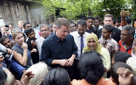 Britain's Prime Minister David Cameron talks with Tamil people at the Sabapathi Pillay Welfare Centre in Jaffna, about 400 km (250 miles) no