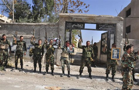 Soldiers loyal to Syria's President Bashar al-Assad raise their weapons while carrying pictures of him at Sbeineh town, southern Damascus, a