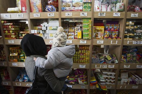 A woman carrying her son stands in front of a food shelf as she shops at a supermarket in northern Tehran, December 12, 2011. REUTERS/Mortez