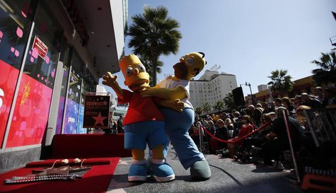 "The characters of Homer (R) and Bart Simpson pose by the star of Matt Groening, creator of ""The Simpsons,"" before it was unveiled on the Wal"
