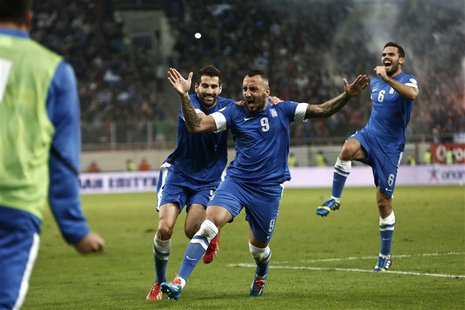 Greece's Kostas Mitroglou (C), Dimitris Siovas (L) and Alexandros Tziolis celebrate a goal against Romania during their 2014 World Cup quali