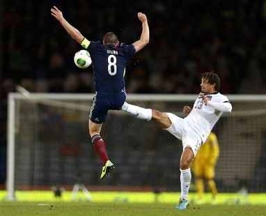 Scotland's Scott Brown (L) is tackled by Jermaine Jones of the U.S. during their international friendly soccer match at Hampden Park Stadium