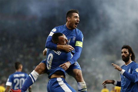 Greece's Kostas Katsouranis (top) jumps onto Kostas Mitroglou as they celebrate Mitroglou's goal against Romania during their 2014 World Cup