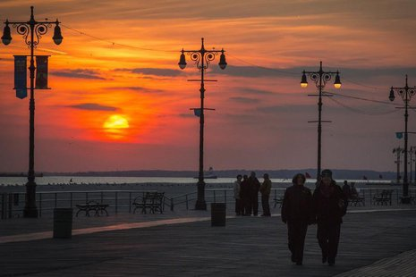 People walk at the Coney Island boardwalk during sunset on the one-year anniversary of Hurricane Sandy in the Brooklyn borough of New York,