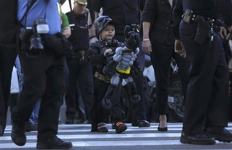 "Five-year-old leukemia survivor Miles Scott, dressed as ""Batkid"" looks at a Batman balloon after a ceremony arranged by the Make- A - Wish F"