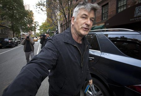 Actor Alec Baldwin shoves a photographer and tells him to move out of his way after he arrived in his SUV at the building where he lives in