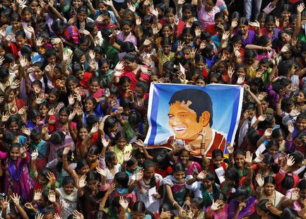 School children wave as they hold a poster of Indian cricketer Sachin Tendulkar at an event to honour him inside a school in the southern In