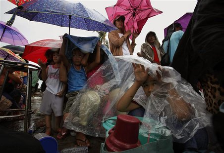 Residents shelter from the rain as they wait to get onto a military plane during an evacuation at Tacloban airport in the Typhoon Haiyan dev