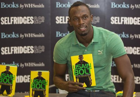 "Jamaican athlete Usain Bolt poses for photographers with a copy of his autobiography, ""Faster than Lightning,"" at Selfridges in central Lond"
