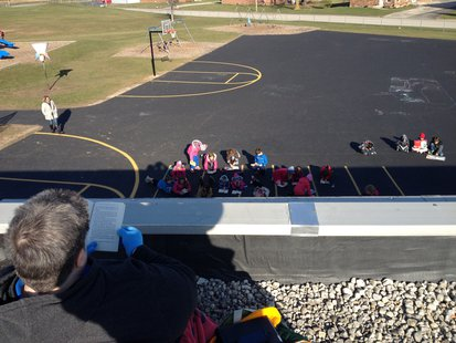 Random Lake third graders read in the playground to encourage Principal Sandra Mountain while she reads on the roof for National Young Reader's Week.
