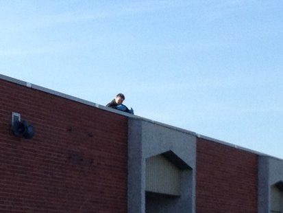 A view of Random Lake Elementary Principal Sandra Mountain from the ground as she reads on the roof, part of a challenge for National Young Reader's Week.