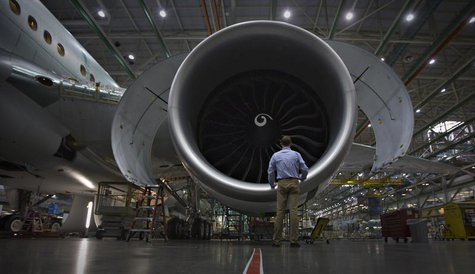 A worker stands in front of an engine on the Boeing 777 at their assembly operations in Everett, Washington, October 18, 2012 file photo. RE