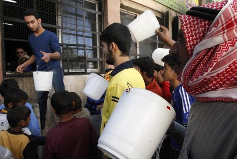 Residents carry buckets as wait for their turn to receive free meals from a soup kitchen in the city of Raqqa, eastern Syria October 7, 2013