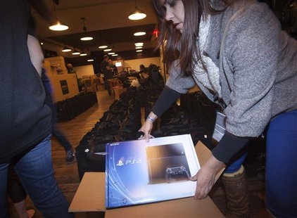 A Sony employee takes a Playstation 4 out of the box in advance of a special sale event put on by Sony at the Standard Hotel in New York Nov