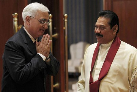 India's Foreign Minister Salman Khurshid (L) gestures next to Sri Lanka's President Mahinda Rajapaksa as he arrives for a banquet dinner for