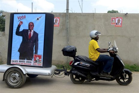 A supporter of the ruling Frelimo party rides a motorcycle with an election poster in tow in the capital Maputo November 16, 2013. Mozambiqu