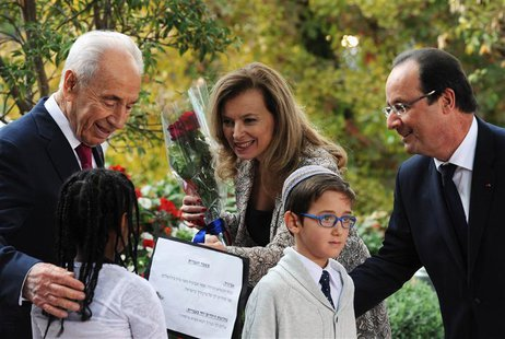 French President Francois Hollande (R) and his companion Valerie Trierweiler stand next to Israeli President Shimon Peres (L) as students fr