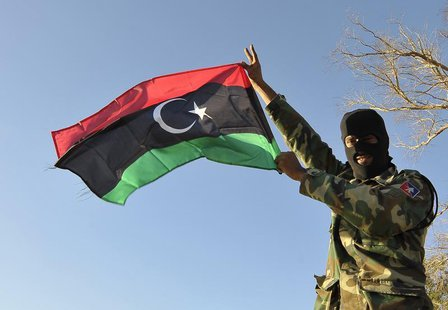 A member of the Libyan army's Thunderbolt Brigade flies the Libyan flag as the army prepares for deployment in Benghazi, November 8, 2013. R