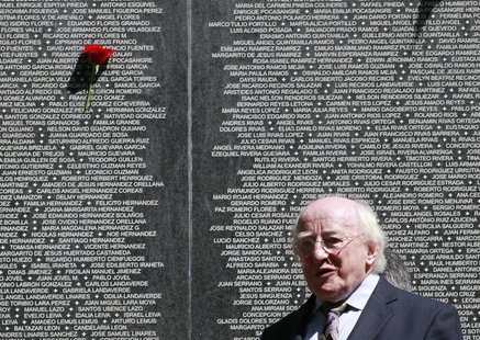 Ireland's President Michael D. Higgins stands in front of a monument for people who disappeared during the Salvadoran Civil War, in Cuscatla