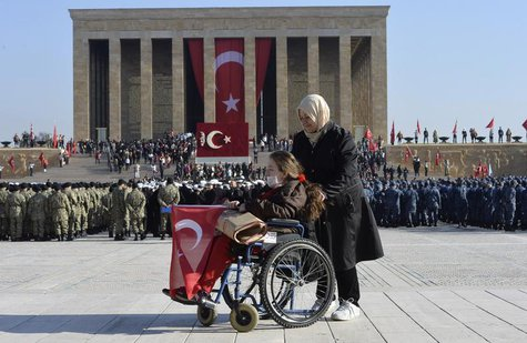 A woman holds the Turkish national flag at the mausoleum of Mustafa Kemal Ataturk, the first president of Turkey and founder of the modern s