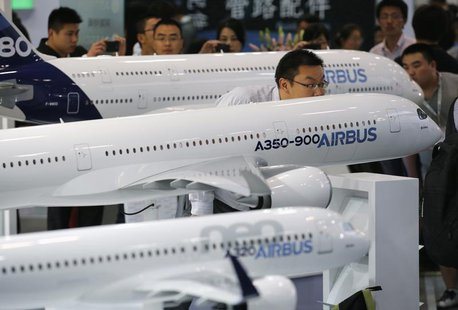 A visitor looks at a miniature Airbus A350-900 passenger aircraft at Aviation Expo China 2013 in Beijing September 25, 2013. REUTERS/Kim Kyu