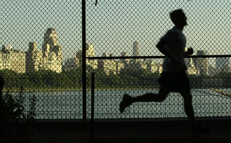 A man jogs along a path around the Central Park Reservoir with the buildings of Fifth Avenue in the backround in New York's famed Central Pa