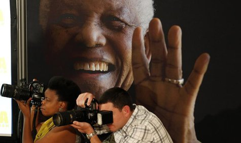 Photographers take pictures in front of a poster of anti-apartheid leader and former president Nelson Mandela during a news conference with