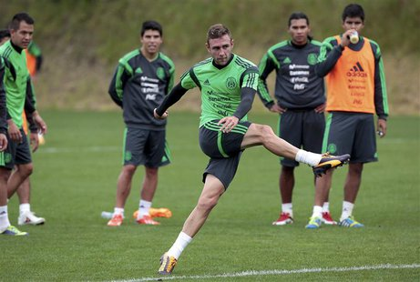 Mexico's Miguel Layun is watched by his team mates as he kicks a ball at a training session for their 2014 World Cup qualifying playoff seco