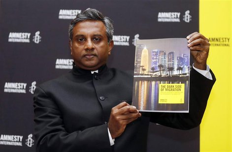 "Amnesty International Secretary General Salil Shetty holds up a report titled ""The Dark Side of Migration: Spotlight on Qatar's construction"