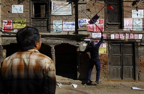 A police personnel recruited for the Constituent Assembly election, removes a party flag near the polling station a day before the election