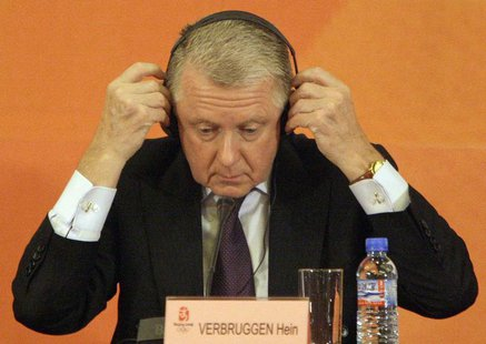 Hein Verbruggen, Chairman of the International Olympic Committee (IOC) Coordination Commission, puts on his headphones during a news confere